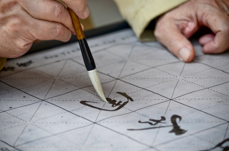 The hands of an elder person writing Chinese calligraphy photo