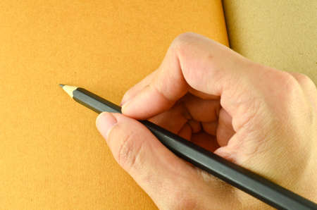 Human hand holding a pencil,ready to write photo