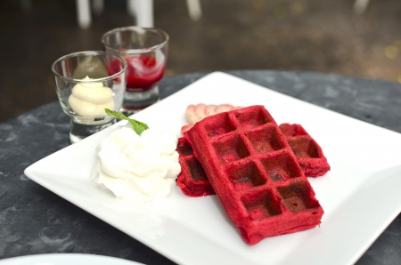 Canberry waffle served with cream and strawberry sauce photo