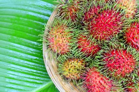 Rambutan in the basket placing on green leaf