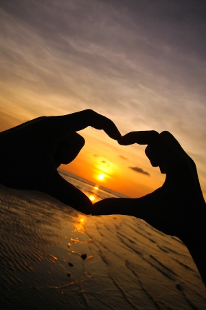 Silhouette heart from hand at sunset Banco de Imagens