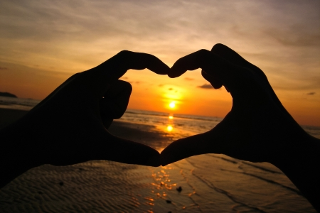 Silhouette heart from hand at sunset Stock Photo