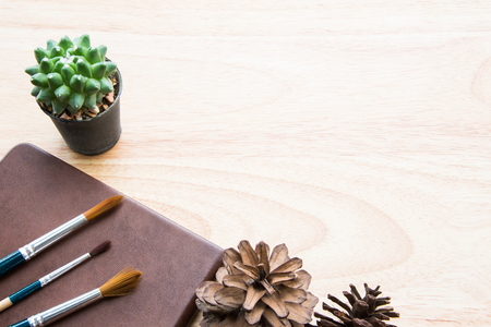 Brown tone table decoration with green cactus and paintbrush: copy space