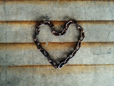 beatification: old chain heart-shaped on cement floor for background