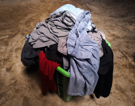 cleaned: pile of dirty clothes in green basket on cement floor Stock Photo
