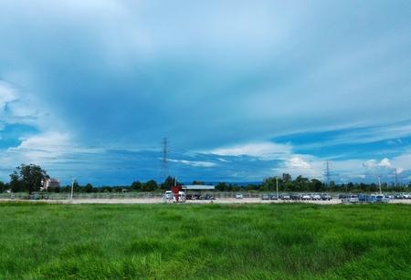 car park beside green rice field under cloudy blue sky