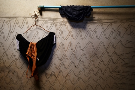 brown bra and black underwear on hanger and black underware on blue pipe and dirty cement wall for background