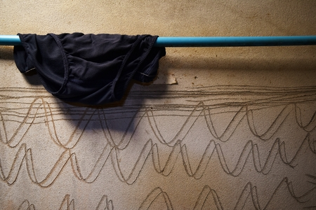 black underware on blue pipe and dirty cement wall for background Stock Photo