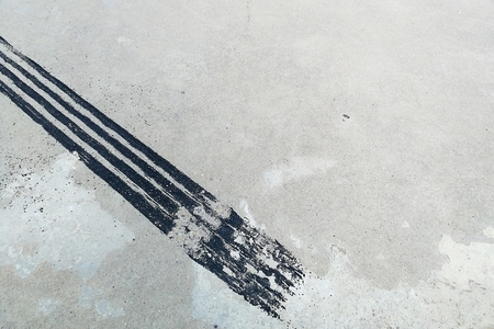 black tire track on dirty concrete after sudden brake Stock Photo