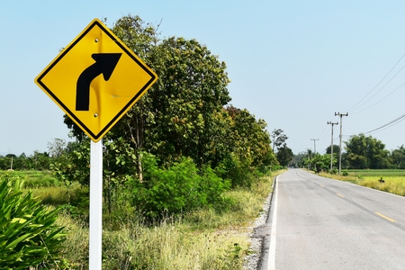 old and dirty traffic signs beside asphalt road in countryside Banco de Imagens