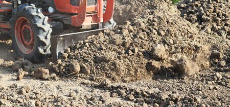 tractor push clot soil after pour from truck