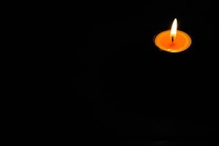 votive: candle light of warm glowing candles on dark background Stock Photo