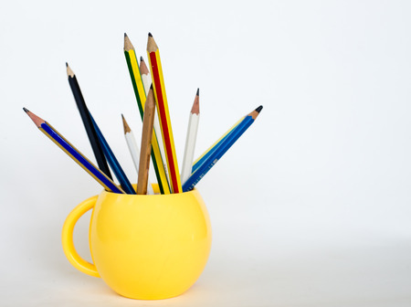 surpass: Group of pencils  in yellow cup.