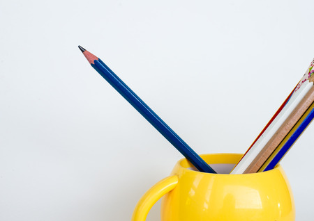 Group of pencils  in yellow cup.