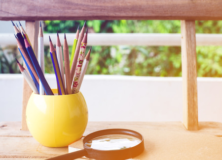Group of pencils and notebook on wood background.