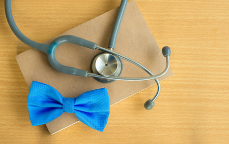 stetoscope: Blue bow with stetoscope  close up on notebook.