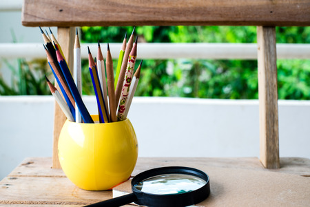 surpass: Group of pencils and notebook on wood background.