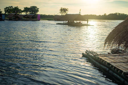 house float on water: bamboo rafting travel in thailand.sunset
