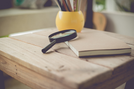 Magnifying Glass and pencil in vintage tone.