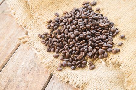 planta de cafe: Granos de caf� en el fondo de madera