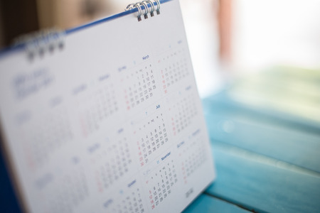 yearly: Blurred calendar page blue background. Stock Photo