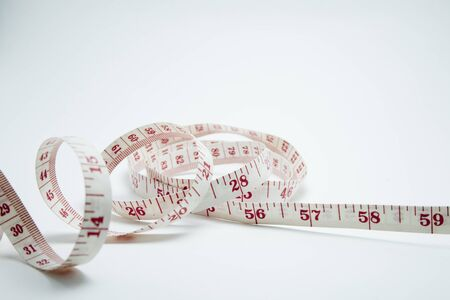 measurement tape: Curved measuring tape. Measuring tape of the tailor. Closeup view of white measuring tape