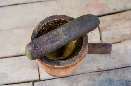 cooking utensil: mortar on wood background