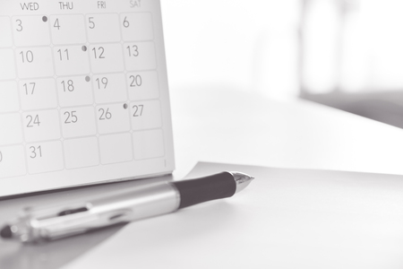 flicking: blurred calendar with pen in planning concept.