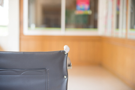 disablement: Empty wheelchair parked in hospital with selective focus. Stock Photo