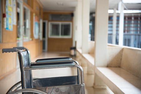 Empty wheelchair parked in hospital with selective focus. Stock Photo