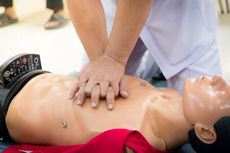 compressions: CPR training medical procedure - Demonstrating chest compressions on CPR doll in the class