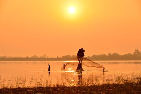 fisherman on silhouette sunset background. Stock Photo