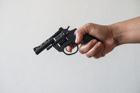 Hand shooting gun on white background killer concept.