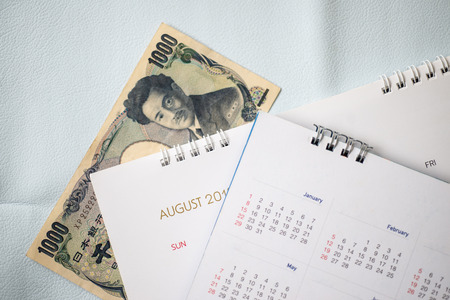Close up Japan banknote with calendar in travel planning concept.