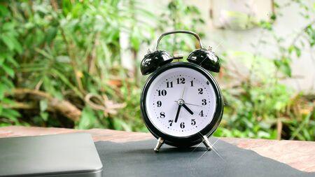 Vintage clock on wood table work space in green garden. 版權商用圖片