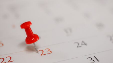 Close  up red pin marked on calendar in planning concept.