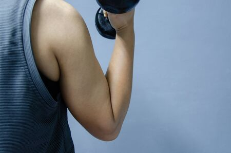 Hand  with black dumbbell on gray background in healthty concept. Stock Photo