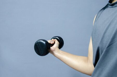 Hand  with black dumbbell on gray background in healthy concept.