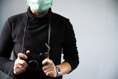 Photographer with black camera film on grey background. 版權商用圖片