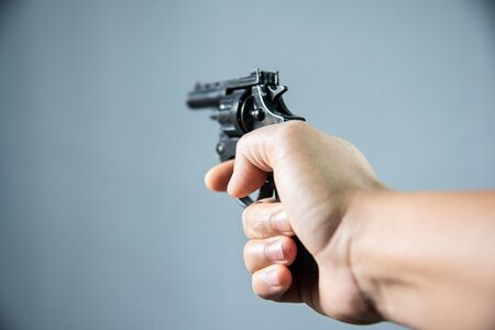 Gun in hand on grey background.Crime concept. Stock Photo