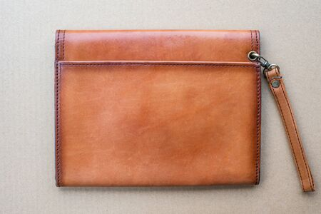 Close up brown leather wallet on wood texture.