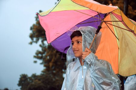 A indian boy looking the other way, wearing rainbows in wet water, with colorful umbrella, village view. Stockfoto