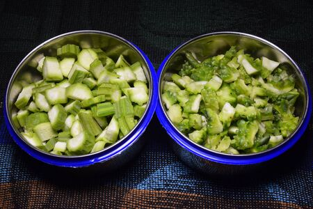 Fresh bitter gourd and okra fruits pieces in two bowls,