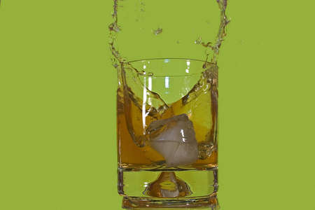 Ice floe falling into whisky glass causing from the splashes