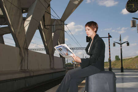 woman reading her newspaper sitting on its luggage