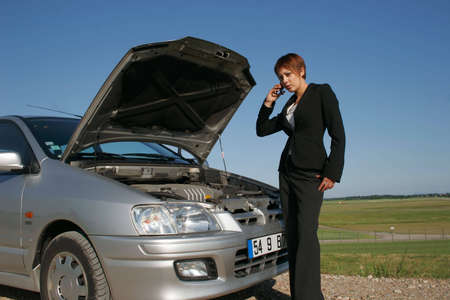 Woman breaking down of car and discussing with her telephone