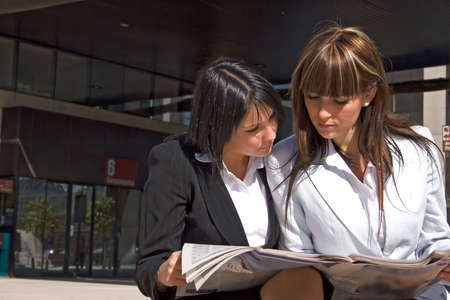 agglomeration: Portrait of two women reading the newspaper together Stock Photo