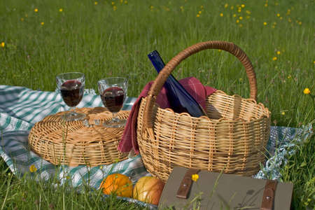 Basket of picnic in grass posed on a tablecloth