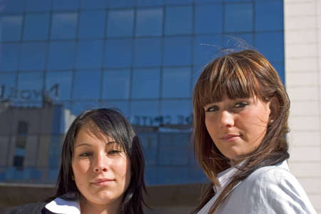 facilitated: Portrait of two young women with lbuilding behind