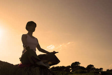 woman making of yoga at the sunset